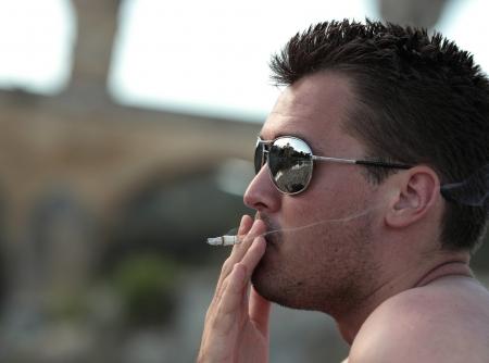 habit: Deadly nasty habit - Male smoker wearing sunglasses smoking a cigarette outdoors