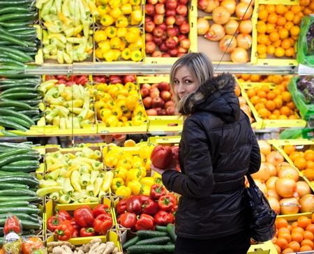 produce sections: Pretty young blond woman shopping for fruit and vegetables in a supermarket Stock Photo