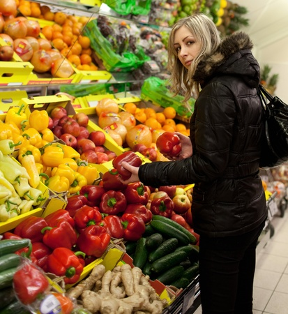 Beautiful young woman shopping for fruits and vegetables at a supermarket photo