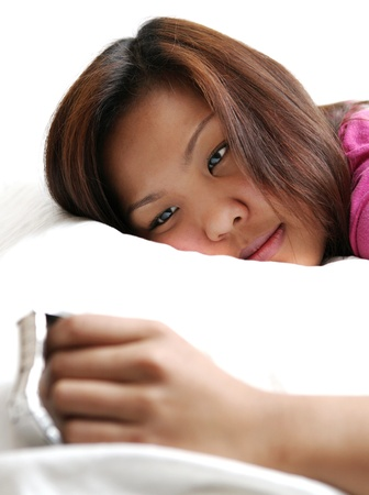 Insommnia - young asian woman looking at her watch, unable to fall asleep Stock Photo - 9804164