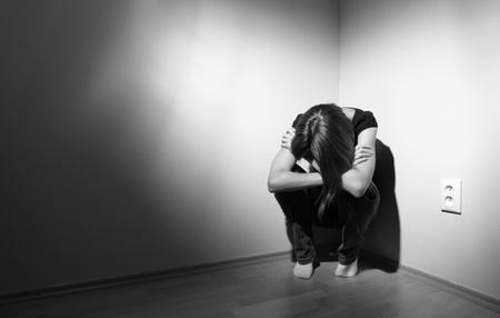 depressione: Giovane donna soffre di una grave depressione (molto dura illuminazione viene utilizzato su questo colpo per sottolineare  trasmettere l'umore cupo della scena) Archivio Fotografico