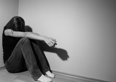 Young woman suffering from a severe depression (very harsh lighting is used on this shot to underline/convey the gloomy mood of the scene) Stock Photo - 9800194