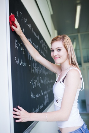 pretty, young college student erasing the chalkboardblackboard during a math class  photo