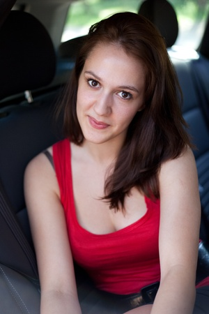 Close-up portrait of a pretty young smiling brunette sitting on a backseat of a car photo