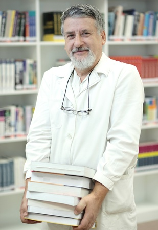 book racks: Renowned scientistdoctor in a library of research centerhospital holding many books and looking confident