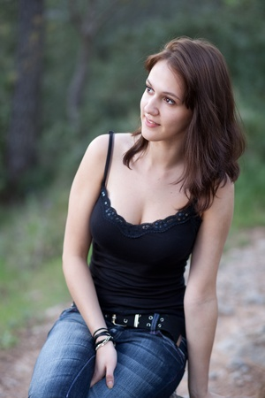 Portrait of a very pretty young brunette woman outdoors sitting on a small wall Stock Photo - 9792824