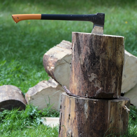 Chopping wood - ax in a log outdoors photo