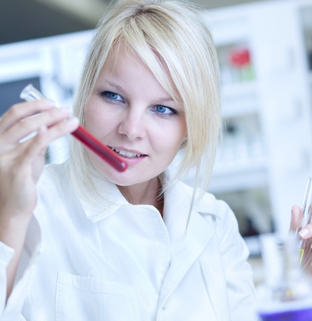 Closeup of a female researcher holding up a test tube and a retort and carrying out some experiments photo