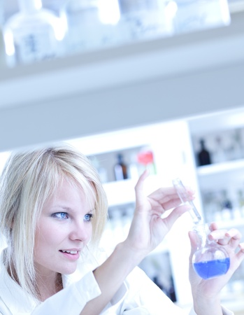 Closeup of a female researcher holding a test tube and a retort and carrying out experiments in a laboratory Stock Photo - 9793862