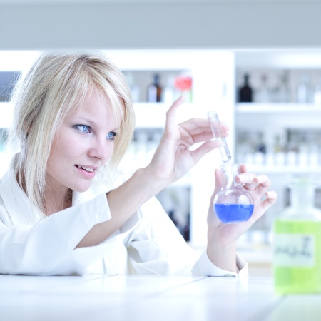 Closeup of a female researcher holding a test tube and a retort and carrying out experiments in a laboratory photo