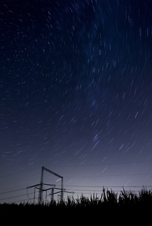 starry night landscape with high voltage poles