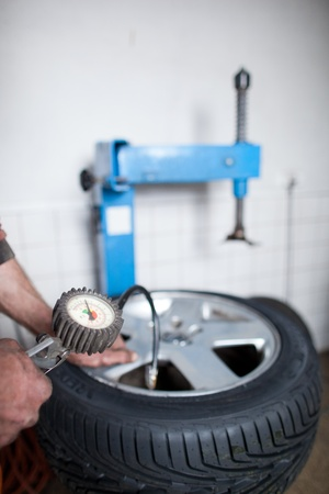 tire repair shop: mechanic changing a wheel of a modern car (shallow DOF; color toned image) Stock Photo