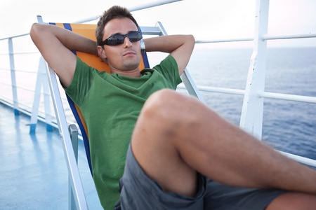 far away look: Young man resting on a deckchair while traveling on a liner across a seaocean