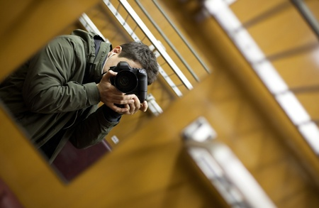 young man on a train taking a self portrait with the able assistance of a mirror photo