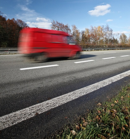 Red deliverycargo van going fast on a highway photo