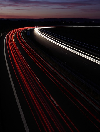 proceed: Cars in a rush moving fast on a highway (speedway) at dusk