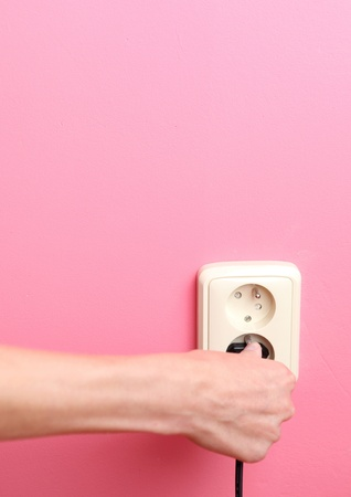 wall socket: Young womans hand plugging a power plug into an electric wall socket at a pink wall