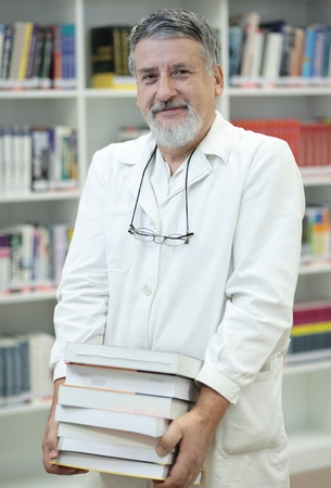 Renowned scientistdoctor in a library of research centerhospital holding many books and looking confident photo