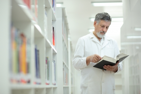 investigador cientifico: Renombrado cient�fico y m�dico en una biblioteca de investigaci�n Centrohospital - navegando en un libro Foto de archivo