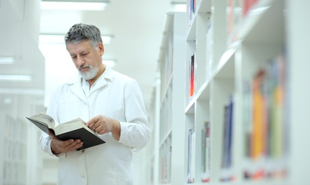 books new books: Renowned scientistdoctor in a library of research centerhospital - browsing a book Stock Photo