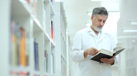 book racks: Renowned scientistdoctor in a library of research centerhospital - browsing a book Stock Photo