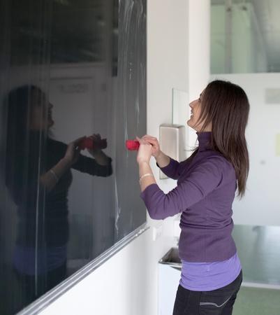 pretty young college student erasing the chalkboardblackboard in a classroom photo