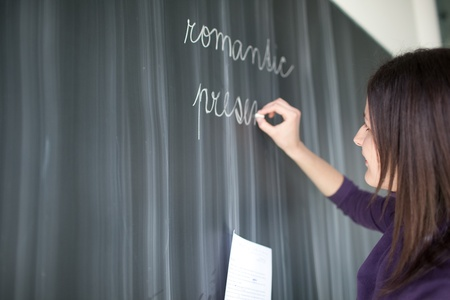 pretty young college student writing on the blackboard during a literature class photo