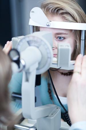 sight chart: concepto de Optometr�a - bastante joven tener ojos examinados por un m�dico de ojos Foto de archivo