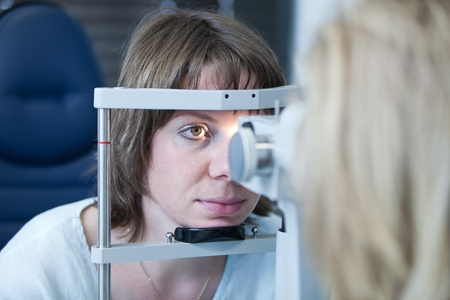 doctor of optometry: optometry concept - pretty young woman having her eyes examined by an eye doctor