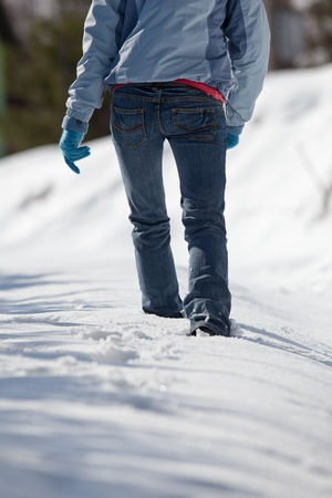pretty young woman walking in deep snow on a sunny winter day photo