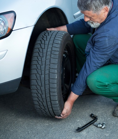 mechanic changing a wheel of a modern car (color toned image) Stock Photo - 9907106