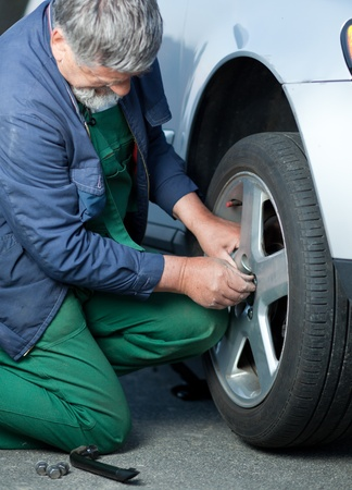 mechanic changing a wheel of a modern car (color toned image) Stock Photo - 9906866