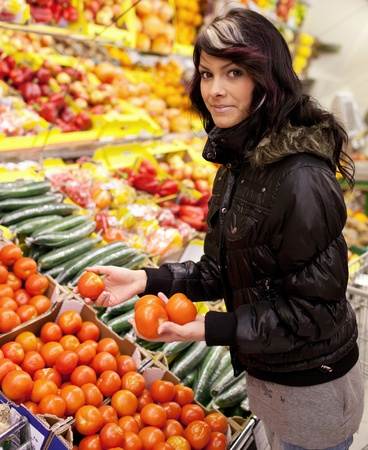 Beautiful young woman shfruits and vegetables at a supermarketgrocery photo