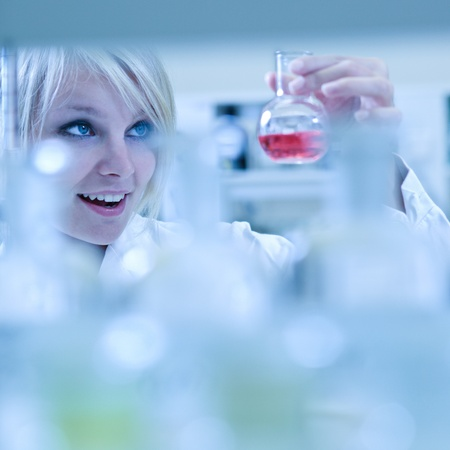 titration: Closeup of a female researcher carrying out experiments in a laboratory  - looking surprised