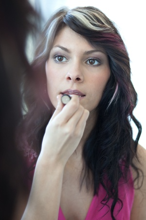 pretty young woman applying mascara eyeshadows in front of a mirror photo