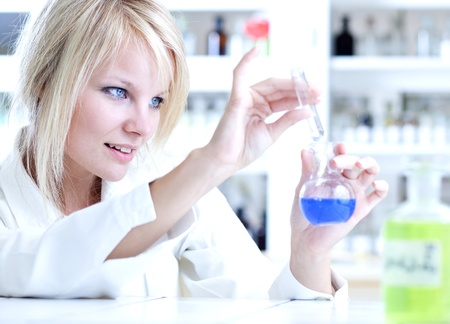 Closeup of a female researcher holding up a test tube and a retort and carrying out experiments Stock Photo - 9906603
