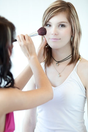 pretty young woman having powder applied by a make-up artistbeautician photo
