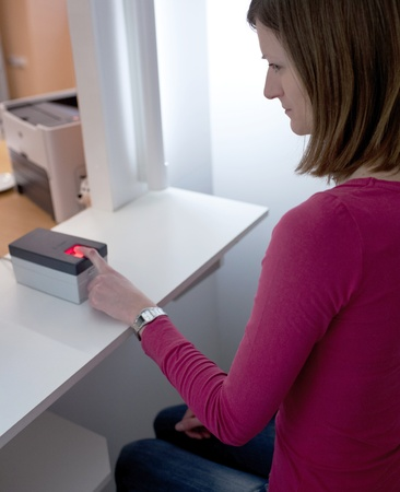 young woman having her fingerprints scanned photo