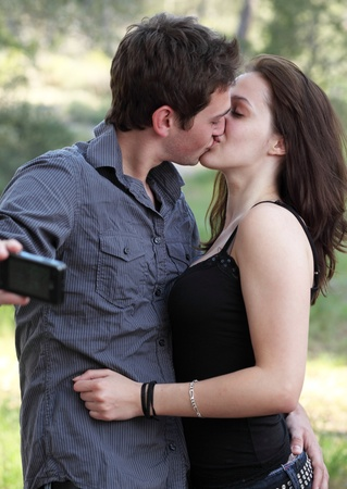 passionately: Beautiful young couple outdoors in a park taking a self-portrait while kissing passionately