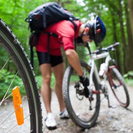 Mountain Bike en un bosque - moteros sobre una pista de ciclismo forestal (DOF superficial, centrarse en la rueda de bicicleta en primer plano) Foto de archivo - 9909578