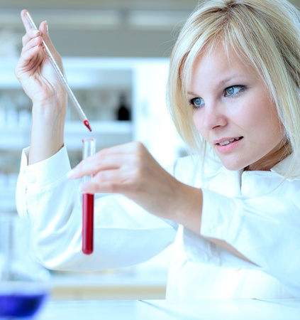 scientific experiment: Closeup of a female researcher holding up a test tube and a retort and carrying out experiments