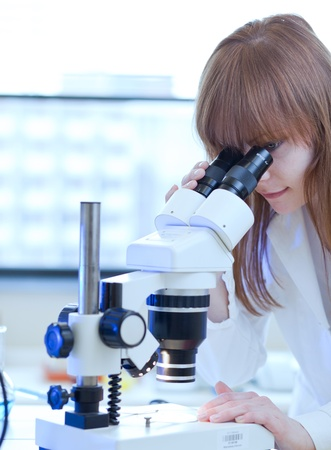 pretty female researcher using a microscope in a lab photo