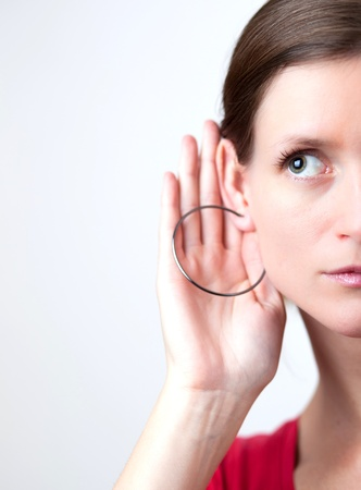 Pretty young woman puts her hand to her ear and listens attentively photo