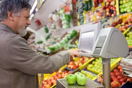 weighing: Handsome senior man shopping for fresh fruit in a supermarket Stock Photo