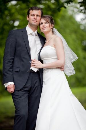 jong bruidspaar - vers trouwen bruidegom en bruid poseren buiten op hun trouwdag