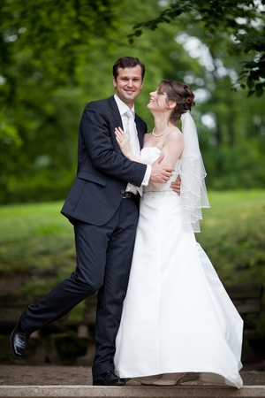 young wedding couple - freshly wed groom and bride posing outdoors on  their wedding day Stock Photo - 9915370