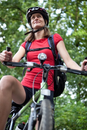 pretty young female biker outddors on her mountain bike (shallow DOF; selective focus) Stock Photo - 9915552