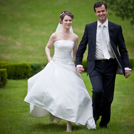 the happy bride: young wedding couple - freshly wed groom and bride posing outdoors on  their wedding day Stock Photo