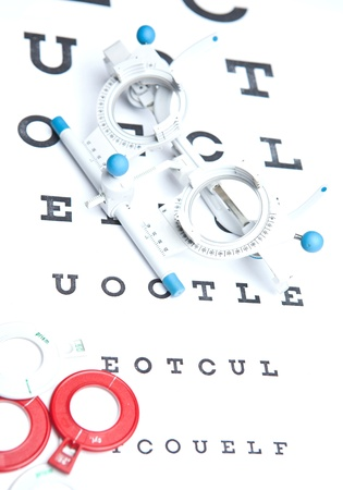 optometry concept - sight measuring spectacles & eye chart photo