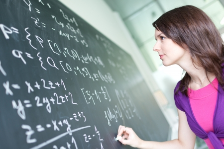 math: pretty young college student writing on the chalkboardblackboard during a math class